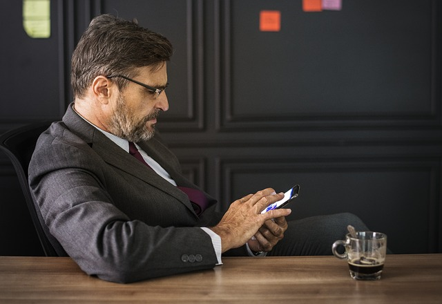 muž v obleku a s telefonem v ruce