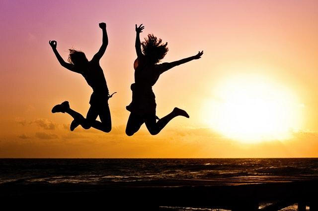 dvě skákající děvčata se západem slunce