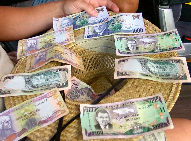 slaměný klobouk ověšený bankovkami